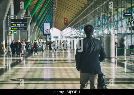 Close up of businessman carrying suitcase while walking through a passenger departure terminal in airport. Businessman traveler journey business trave - Stock Photo