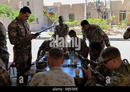 AQABA, Jordan (April 23, 2018) --  1st Lt. Alaa' M.Migdadi with the Jordan Armed Forces Naval Communication Company demonstrates how to use a Harris VHF hand-held radios to U.S. service members, during exercise Eager Lion, April 23, 2018.  Eager Lion is a capstone training engagement that provides U.S. forces and the Jordan Armed Forces an opportunity to rehearse operating in a coalition environment and to pursue new ways to collectively address threats to regional security and improve overall maritime security.  (U.S. Navy photo by Mass Communication Specialist 1st Class Sandi Grimnes Moreno/ - Stock Photo
