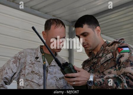 AQABA, Jordan (April 23, 2018) --  1st Lt. Alaa' M.Migdadi with the Jordan Armed Forces Naval Communication Company demonstrates how to use a Harris VHF hand held radio to Staff Sgt. Vitaliy Rusavskiy with Naval Amphibious Force, Task Force 51/5th Marine Expeditionary Brigade, during exercise Eager Lion, April 23, 2018.  Eager Lion is a capstone training engagement that provides U.S. forces and the Jordan Armed Forces an opportunity to rehearse operating in a coalition environment and to pursue new ways to collectively address threats to regional security and improve overall maritime security. - Stock Photo