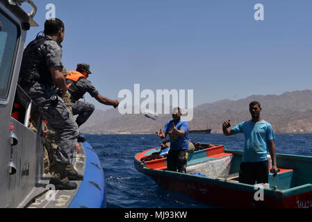 AQABA, Jordan (April 23, 2018) --  Members of the Royal Jordanian Navy Combat Boats Group toss a medical supply kit to local Jordanian fishermen in a civilian outreach event with U.S. Army Civil Affairs during exercise Eager Lion, April 23, 2018.  Eager Lion is a capstone training engagement that provides U.S. forces and the Jordan Armed Forces an opportunity to rehearse operating in a coalition environment and to pursue new ways to collectively address threats to regional security and improve overall maritime security.  (U.S. Navy photo by Mass Communication Specialist 1st Class Sandi Grimnes - Stock Photo