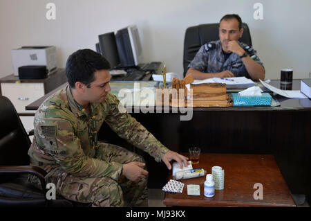 AQABA, Jordan (April 23, 2018) -- U.S. Army Spc. Caleb Dial with U.S. Army Civil Affairs, shows Lt. Cmdr. Mohannad AL-Namat, commanding officer, Royal Jordanian Navy Combat Boats Group,  medical supply kits prior to the outreach event with the local fishermen during exercise Eager Lion, April 23, 2018.  Eager Lion is a capstone training engagement that provides U.S. forces and the Jordan Armed Forces an opportunity to rehearse operating in a coalition environment and to pursue new ways to collectively address threats to regional security and improve overall maritime security.  (U.S. Navy photo - Stock Photo