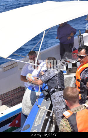 AQABA, Jordan (April 23, 2018) --  Lt. Cmdr. Mohannad AL-Namat, commanding officer of Royal Jordanian Navy Combat Boats Group, hands a medical supply kit to a Jordanian fisherman during a civilian outreach event with U.S. Army Civil Affairs, during exercise Eager Lion, April 23, 2018.  Eager Lion is a capstone training engagement that provides U.S. forces and the Jordan Armed Forces an opportunity to rehearse operating in a coalition environment and to pursue new ways to collectively address threats to regional security and improve overall maritime security.  (U.S. Navy photo by Mass Communica - Stock Photo