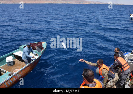 AQABA, Jordan (April 23, 2018) --  U.S. Army Capt. Samuel Edwards, a member of U.S. Army Civil Affairs, tosses a medical supply kit to a Jordanian fisherman during a civilian outreach event with Royal Jordanian Navy Combat Boats Group during Eager Lion, April 23, 2018.  Eager Lion is a capstone training engagement that provides U.S. forces and the Jordan Armed Forces an opportunity to rehearse operating in a coalition environment and to pursue new ways to collectively address threats to regional security and improve overall maritime security.  (U.S. Navy photo by Mass Communication Specialist  - Stock Photo