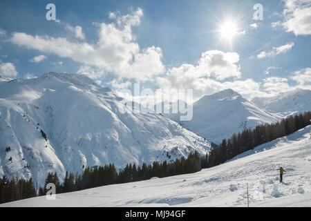 SEDRUN, SWITZERLAND - FEBRUARY 9, 2018: Snowboarder riding down the slope on beautiful sunny winter day in Sedrun ski resort in Switzerland - Stock Photo