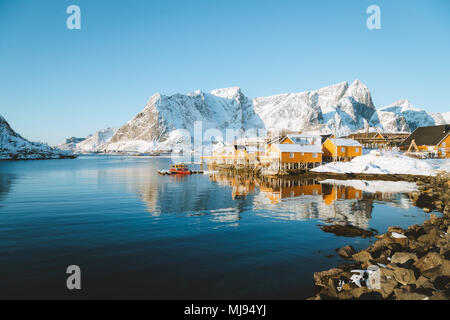 Beautiful Lofoten Islands archipelago winter scenery with traditional yellow fisherman Rorbuer cabins in the historic village of Sakrisoy, Norway - Stock Photo