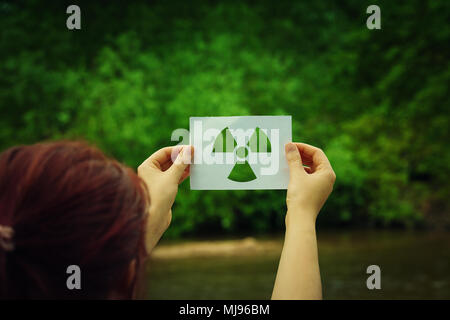 Woman holding a paper sheet with radiation symbol symbol over green forest background. Environmental problems concept, radioactive disaster as danger  - Stock Photo