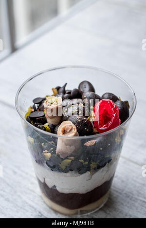 Chocolate Chips Parfait with yogurt in glass cup on white wooden surface - Stock Photo