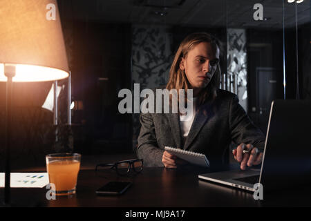 Tired businessman working by the contemporary laptop at night office. Hipster with long hair hold notepad in hand and uses mobile computer. Film effec - Stock Photo