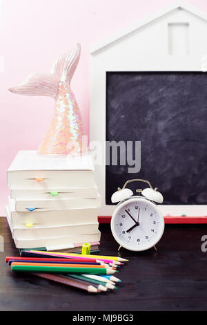 School supplies and alarm clock on table. Back to school concept. - Stock Photo