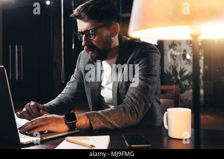 Bearded young businessman working in loft space at night. Coworker sits by the wooden table with lamp and office tools. Project manager using contempo - Stock Photo