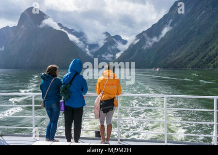 Milford sound New Zealand Milford sound three friends stood at the prow of an excursion boat returning from a boat trip on milford sound  South Island - Stock Photo