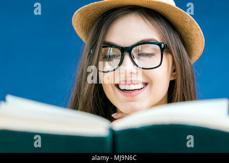 Portrait of beautiful smiling brunette girl wears eyeglasses reading the book with face expression, isolated on blue background - Stock Photo