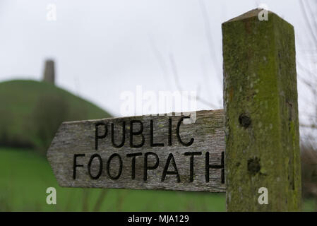 old wooden Public Footpath sign on green weathered post with hill out of focus in the background. - Stock Photo