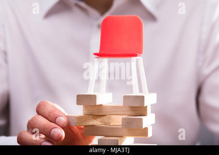Close-up Of A Red Chair Over Human Hand Arranging Wooden Blocks - Stock Photo