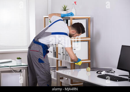Close-up Of A Young Male Cleaner Cleaning Shelf At Workplace - Stock Photo