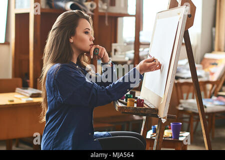 Young beautiful girl, female artist painter thinking of a new artwork idea and ready to make the first brushstroke on a wooden easel with a brush in s - Stock Photo
