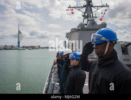 180423-N-UB406-0190 ATLANTIC OCEAN (April 23, 2018) Seaman Benjamin Williams, right, assigned to the guided-missile destroyer USS Farragut (DDG 99), renders honors to the Royal Navy 104-gun first-rate ship HMS Victory as  Farragut enters Her Majesty's Naval Base Portsmouth. Farragut is deployed with the Harry S. Truman Carrier Strike Group. (U.S. Navy photo by Mass Communication Specialist 3rd Class Cameron M. Stoner/Released) - Stock Photo