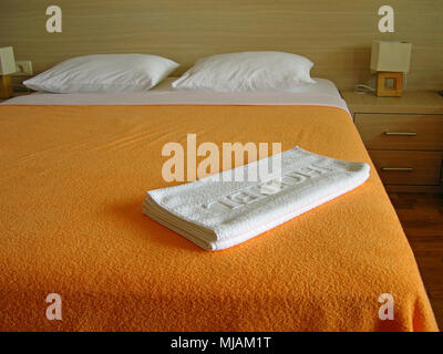 Hotel room with white towels on the bed - Stock Photo
