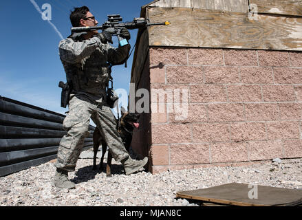 Staff Sgt. Ryne Wilson, 99th Security Forces Squadron military working dog handler, and his MWD, Seneca, clear the outside of a building during a training exercise at Nellis Air Force Base, Nev., April 26, 2018. The exercise tested the team's ability to safely detect and seize explosives. (U.S. Air Force photo by Airman 1st Class Andrew D. Sarver) - Stock Photo