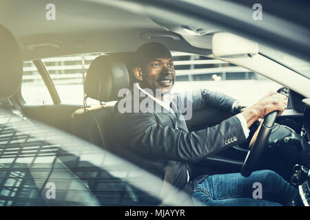 Smiling African businessman wearing a blazer driving his car during his morning commute in the city - Stock Photo