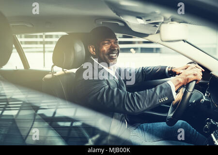 Smiling young African businessman wearing a blazer driving in the city during his morning commute - Stock Photo