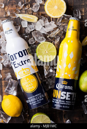 LONDON, UK - APRIL 27, 2018: Steel Bottles of Corona Extra Beer on wooden background with bottle opener and ice cubes. Corona, produced by Grupo Model - Stock Photo
