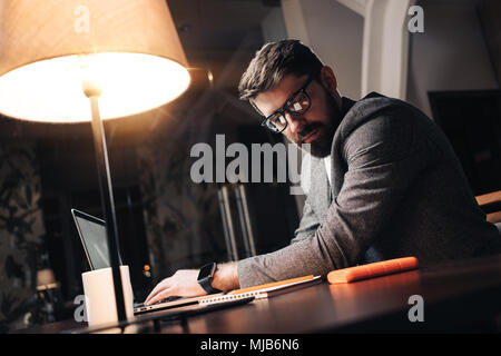 Bearded young businessman in glasses sits by the wooden table with lamp and using contemporary mobile notebook in loft office at night. Coworker worki - Stock Photo