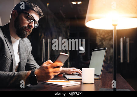 Bearded businessman with laptop using cell phone at the night loft office. Young man typing text on contemporary smartphone. Working process at cowork - Stock Photo