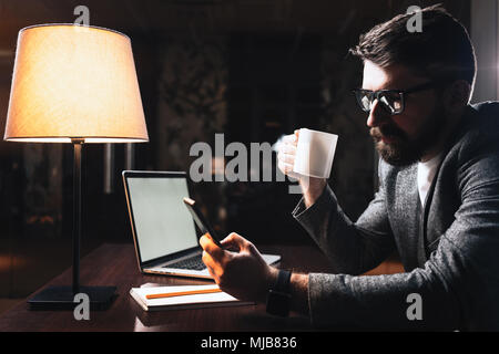 Bearded man hold cup of coffee and using smartphone.Young businessman working at modern office at night - Stock Photo