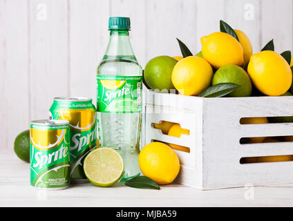 LONDON, UK - APRIL 12, 2017: Bottle and aluminium can of Sprite drink on wooden background with lemons and limes. Sprite is lemon-like flavored soft d - Stock Photo