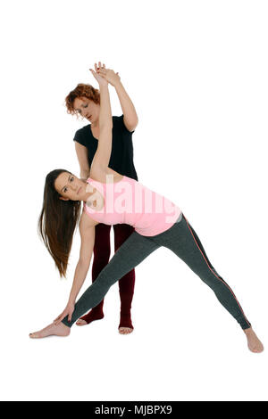 Yoga teacher shows how to put a young white girl in the Yoga position Extended Triangle Pose on sanskrit Utthita Trikonasana. - Stock Photo