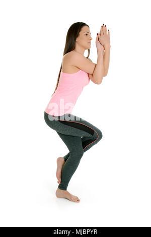 A young white girl performs a yoga asanas. Eagle pose, on sanskrit garudasana. - Stock Photo
