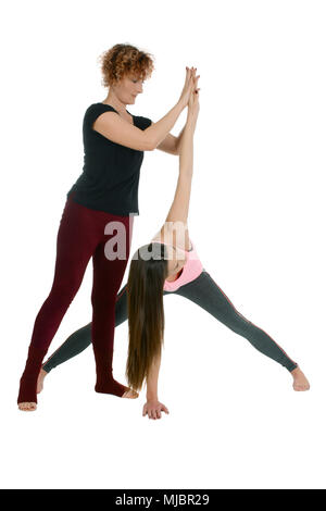 Yoga teacher shows how to put a young girl in the Yoga position Wide-Legged Forward Bend on sanskrit Prasarita Padottanasana variation with twist - Stock Photo