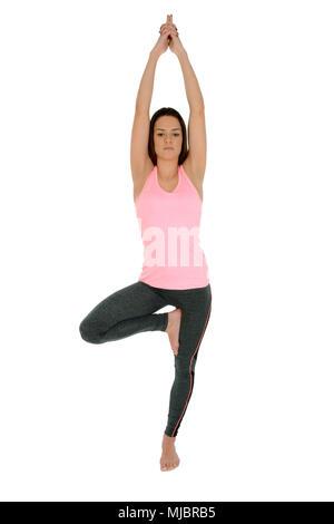 A young white girl performs a yoga asanas Tree Pose,on sanskrit Vrksasana. - Stock Photo