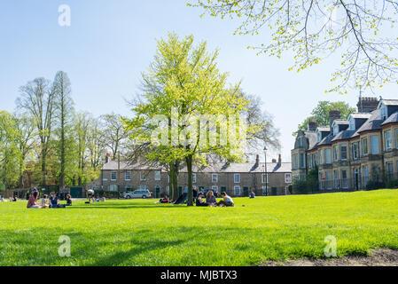 People enjoying the warm spring weather in Jesus Green public park, Cambridge, UK. - Stock Photo
