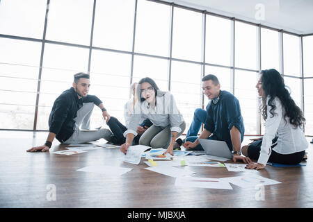 Planning strategy together. Business team looking at papers on floor with manager pointing to one idea. Cooperation corporate achievement. Planning de - Stock Photo