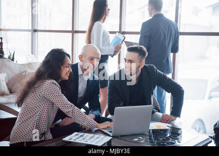 Young team of coworkers making great business discussion in modern coworking office. Teamwork people concept. - Stock Photo