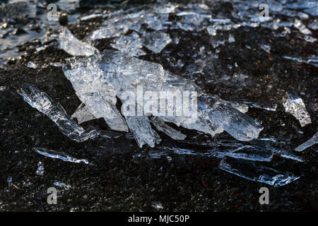 translucent melting ice in spring on the sandy shore of the reservoir closeup - Stock Photo