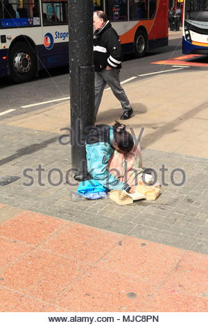 A women in a coat covered with a blanket and reading a book sits on the pavement by a lamp post in Manchester City Centre England May 2018 - Stock Photo