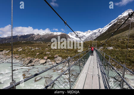MOUNT COOK, NEW ZEALAND - NOVEMBR 18, 2017: A hiker crosses a suspension bridge on the famous Hooker Valley Track in the Mount Cook Aoraki National Pa - Stock Photo
