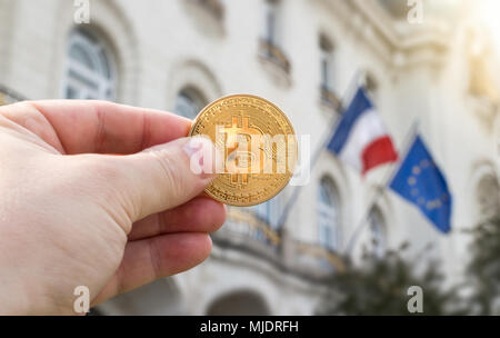Hand holding golden Bitcoin against flags of France and European Union, concept - Stock Photo
