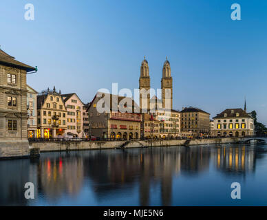 Limmatquai with Grossmuenster, 'Haus zum Rüden' and 'Helmhaus' in the evening at the blue hour - Stock Photo