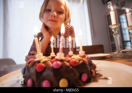 Small girl in front of birthday cake - Stock Photo