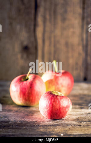 Rural still life: three freshly harvested red apples on an old wooden table - Stock Photo