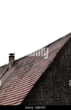 Roof with bricks, fireplace and old shingles, grey weathered on a wooden house in the Black Forest - Stock Photo