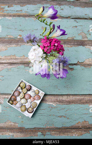 Bouquet from the garden and colorful snail shells - Stock Photo