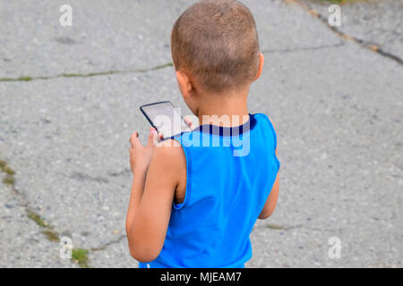 Child with a smartphone. A little boy shoots video on a smartphone - Stock Photo