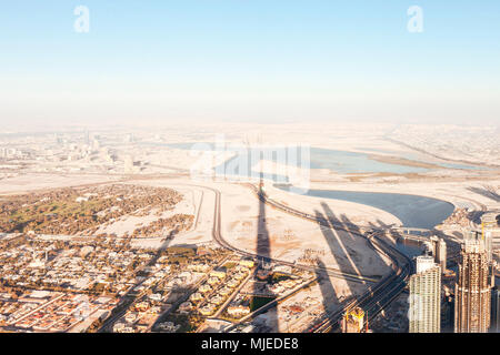 Dubai sunset with shadow of Burj Khalifa - Stock Photo