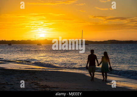 Couple enjoying sunset at Grace bay beach, Providenciales, Turks and Caicos - Stock Photo