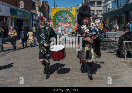 ondon, UK. 5th March 2018. A drummer and a piper lead trade unionists and other socialists on their march through Croydon town centre to a rally at Ruskin House in celebration of May Day, International Workers Day which is celebrated internationally on May 1st.  Unfortunately May Day is not a Bank Holiday in the UK. The marchers were lead through the main shopping street by a piper and drummer in full Scots dress, attracting the attention of shoppers and others on the busy street. I left the march before it reached Ruskin House where there was to be a rally with speakers including Ted Knight.  - Stock Photo